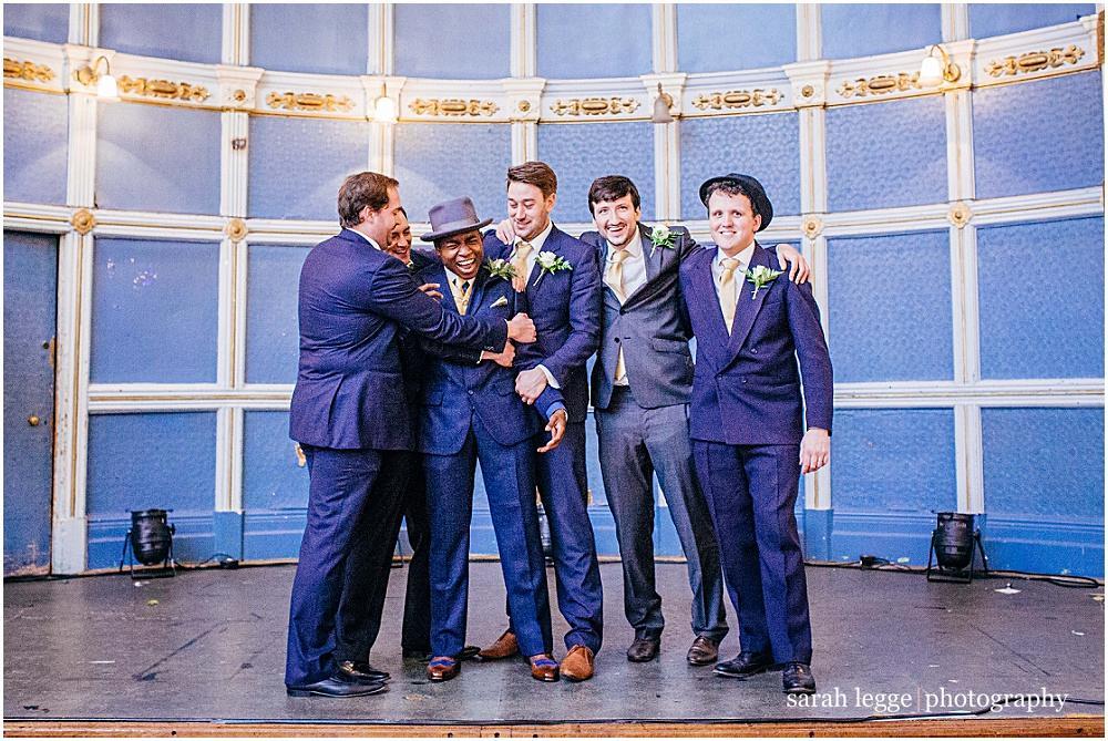 Groomsmen hug groom