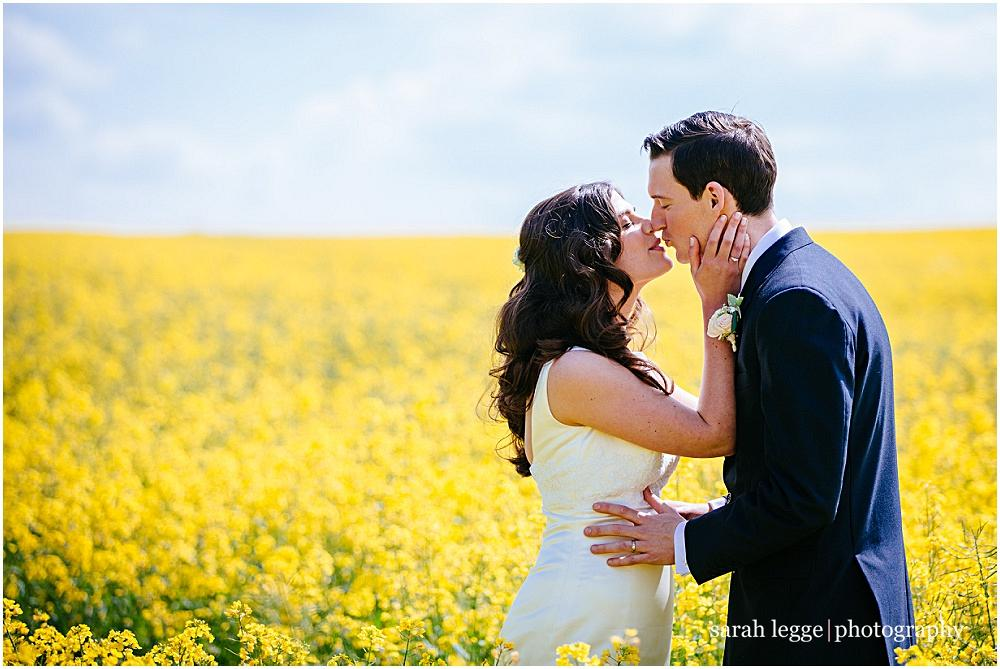 Bride and groom kissing in field of sunshine