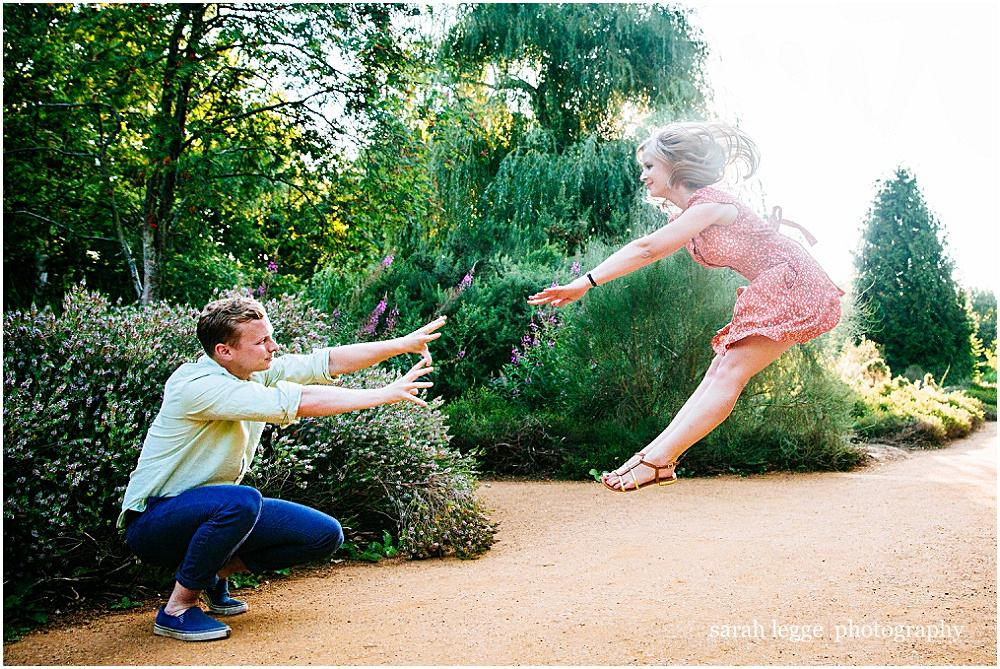 Fun pushing jumping engagement photograph