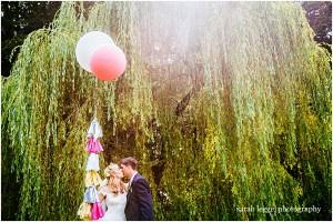 Bride and groom with big balloons and sun flare