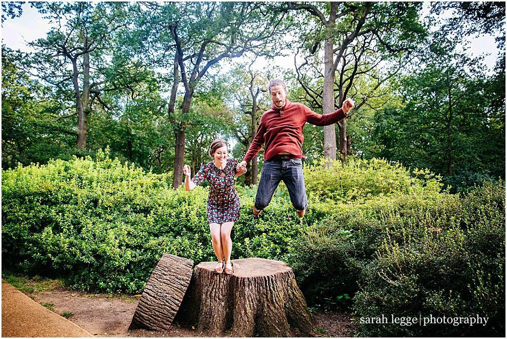 Couple jumping off stump