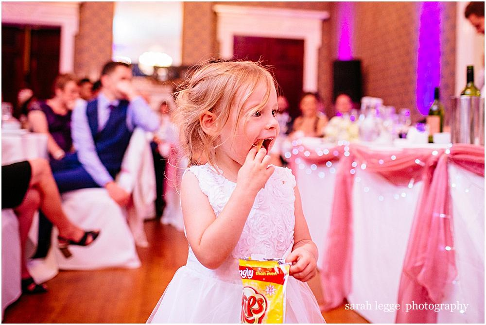 Flower girl eating crisps