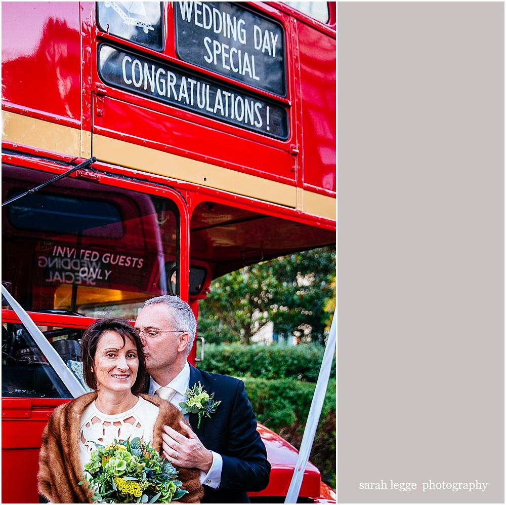 Bride and groom and red vintage bus