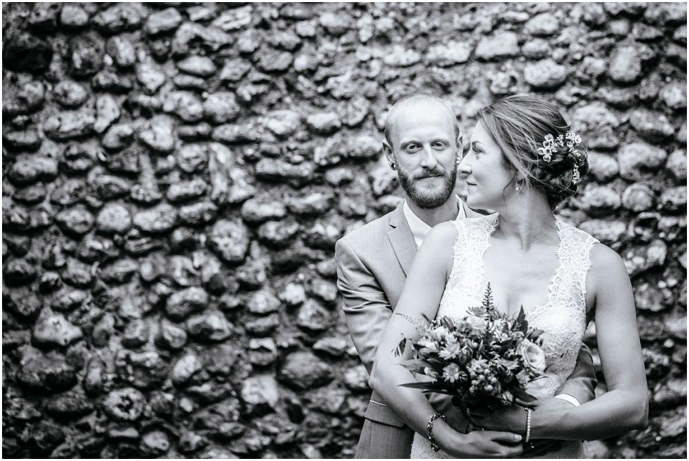 Bride and groom and brick wall