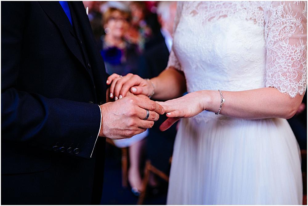 Groom putting wedding ring on
