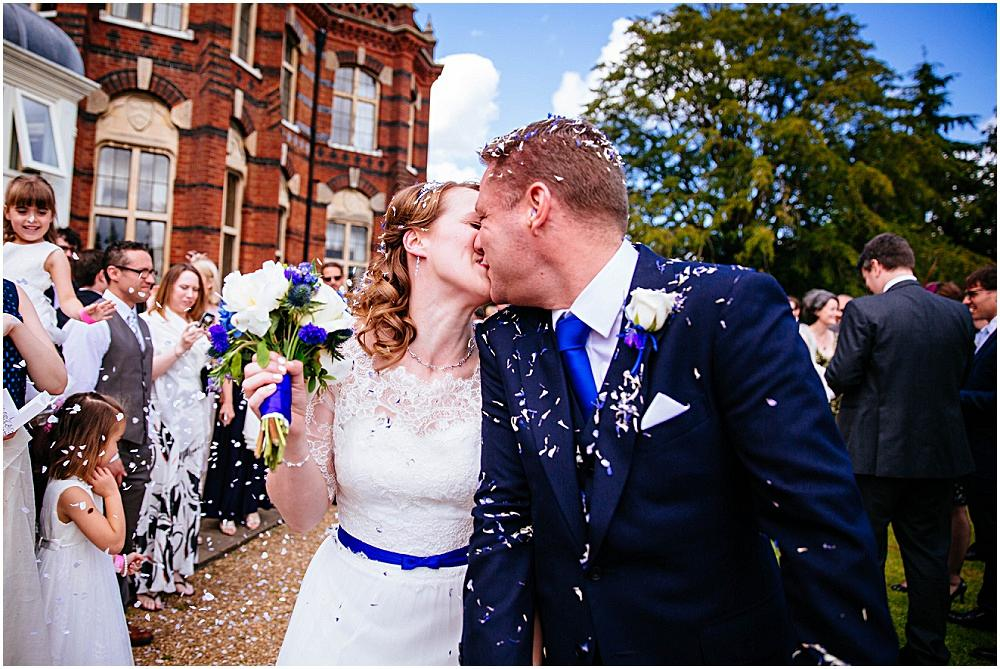 Bride and groom kissing in confetti