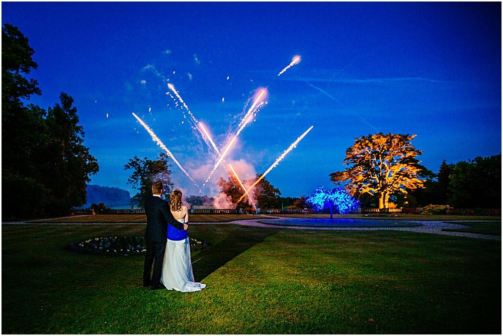 Bride and groom watching fireworks at the elvetham in hampshire