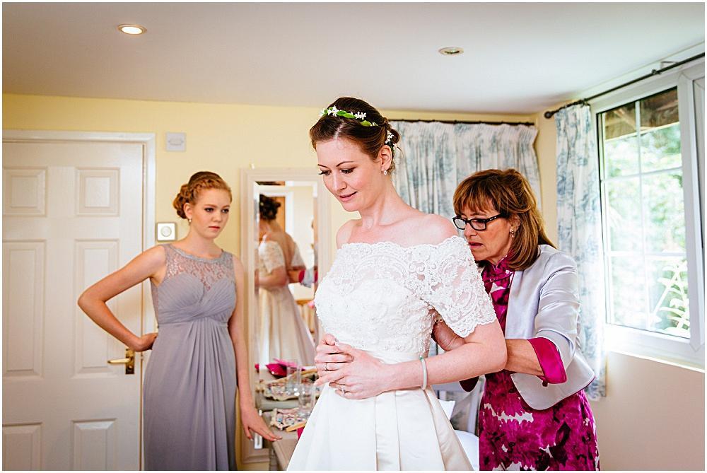 Bride getting into wedding dress at bartholomew barn