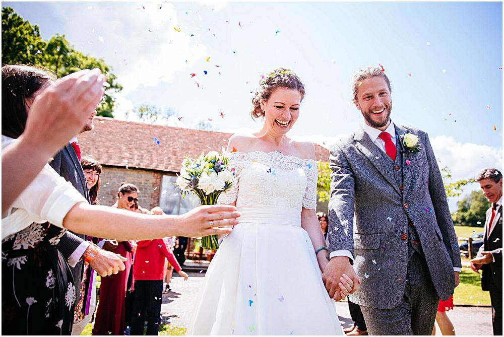 Newlyweds smile at confetti