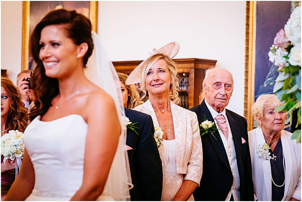 Brides mother looking fondly at bride during wedding ceremony