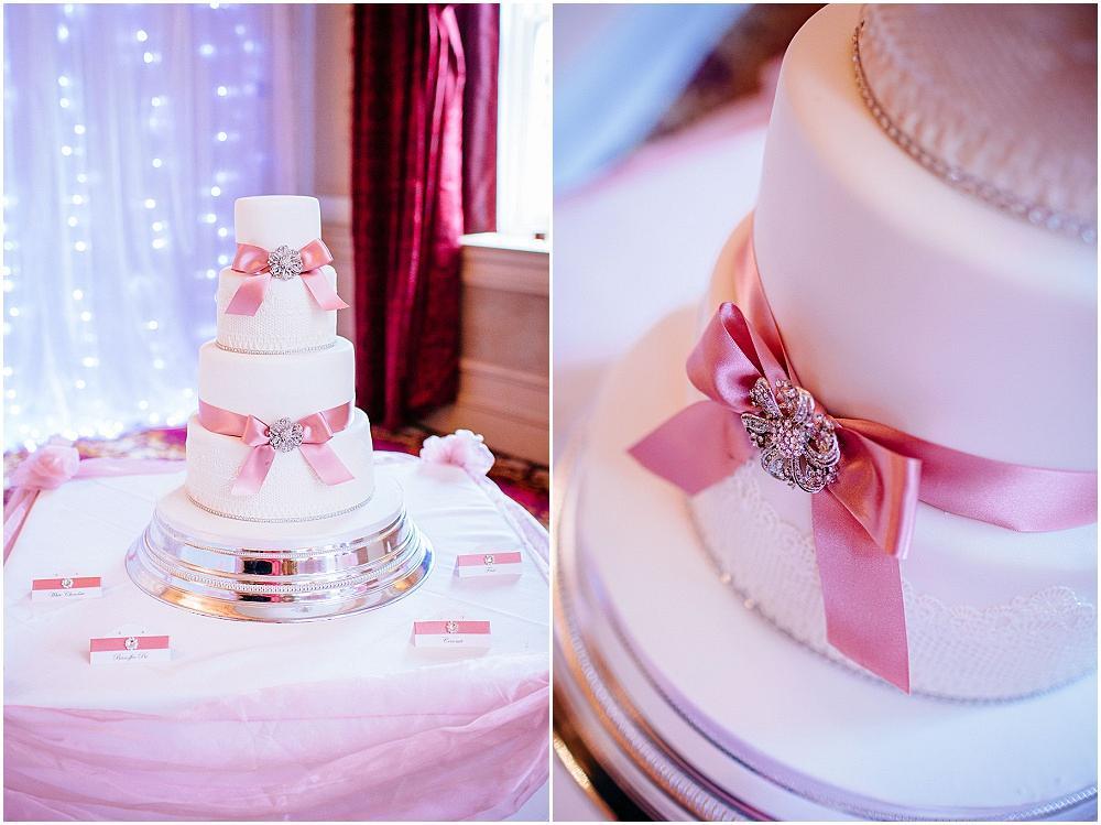 White wedding cake with pink ribbons