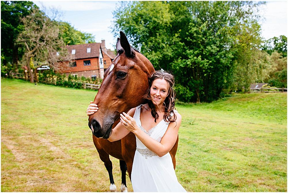 Bride holding her brown horse
