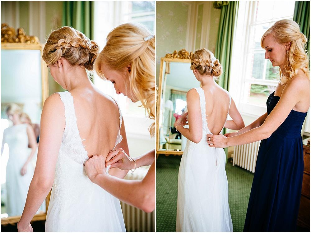 Brides dress being done up at brocket hall