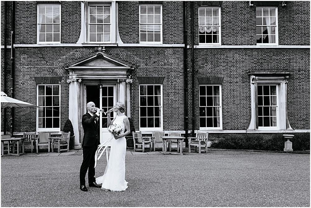 Bride and groom drinking champagne outside brocket hall