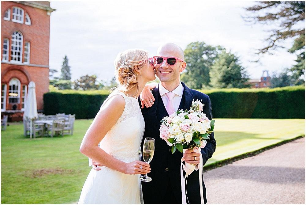 Bride kisses her husband wearing pink sunglasses