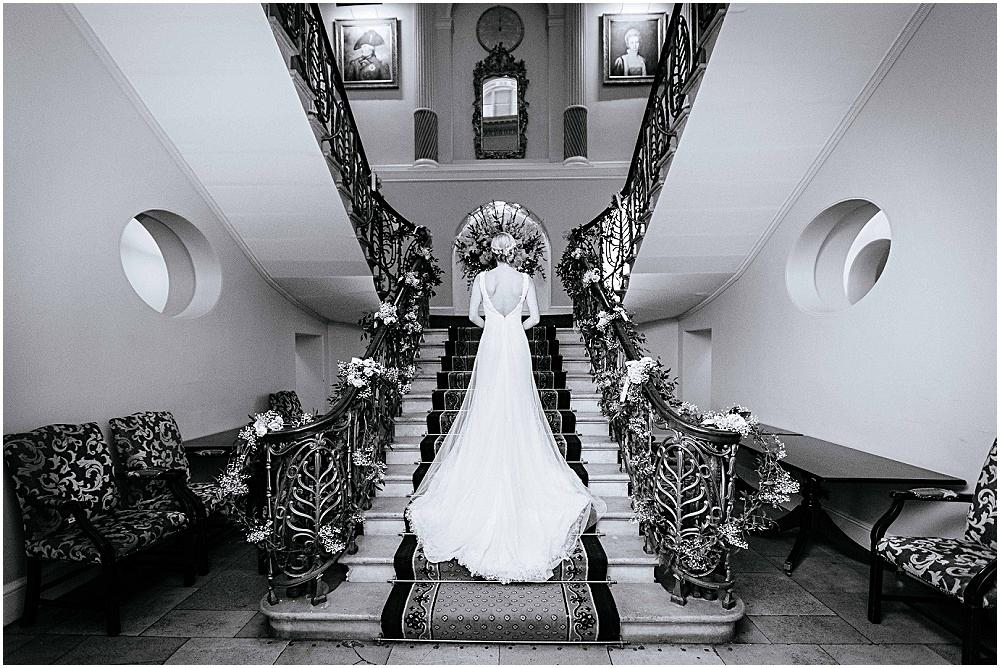 Bride and back of her dress on grand stairs in Brocket Hall
