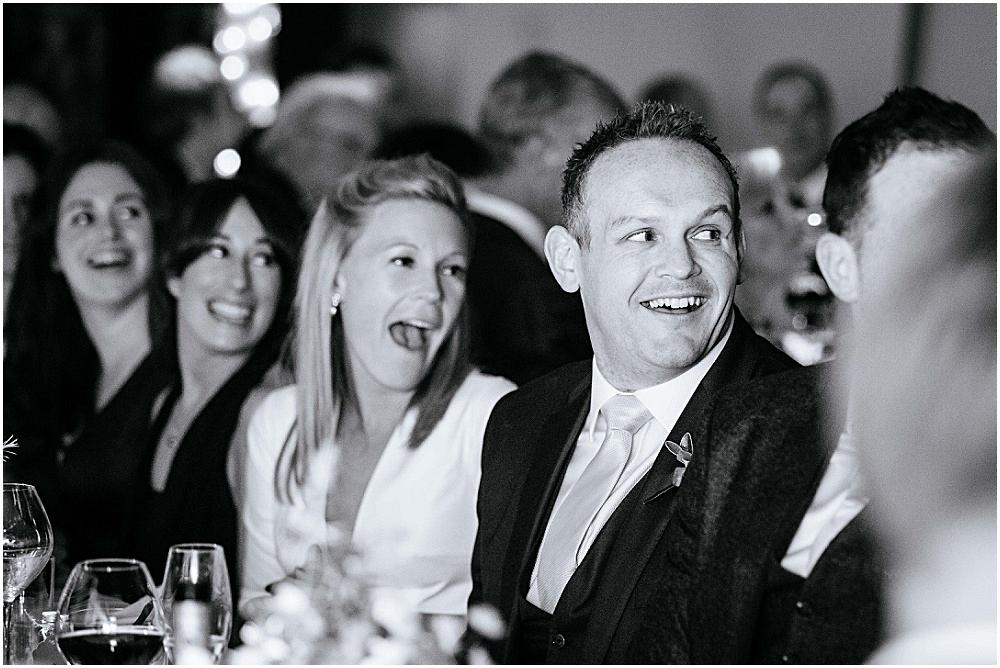Bride and groom laughing at fnny wedding speeches