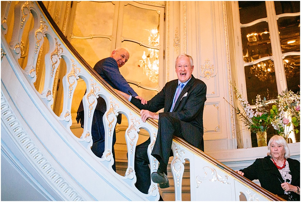 Man sliding down Savile club staircase bannister