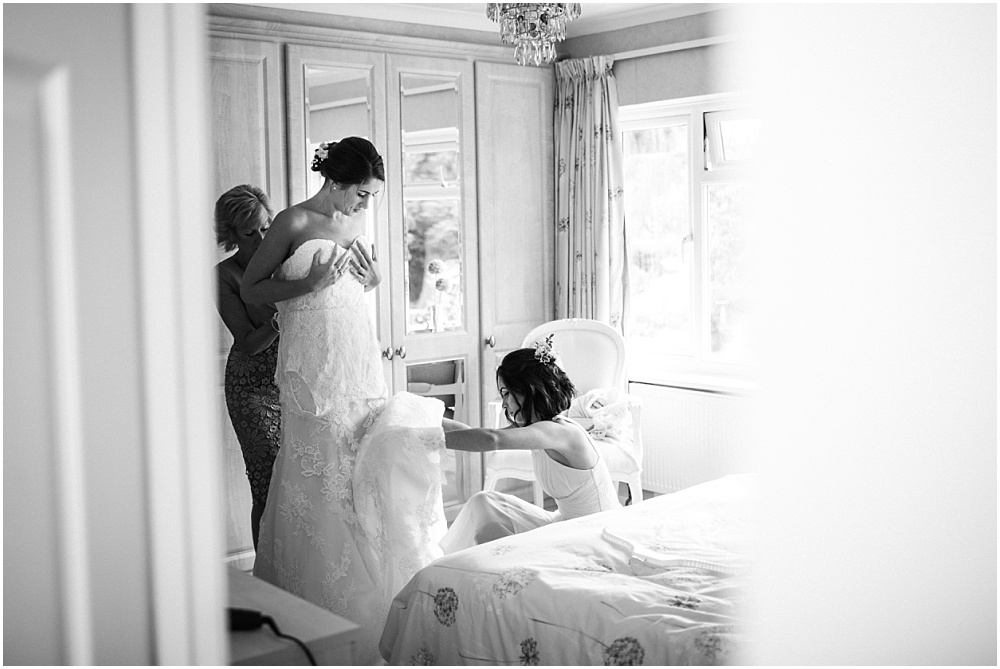 Sister helping bride with wedding dress