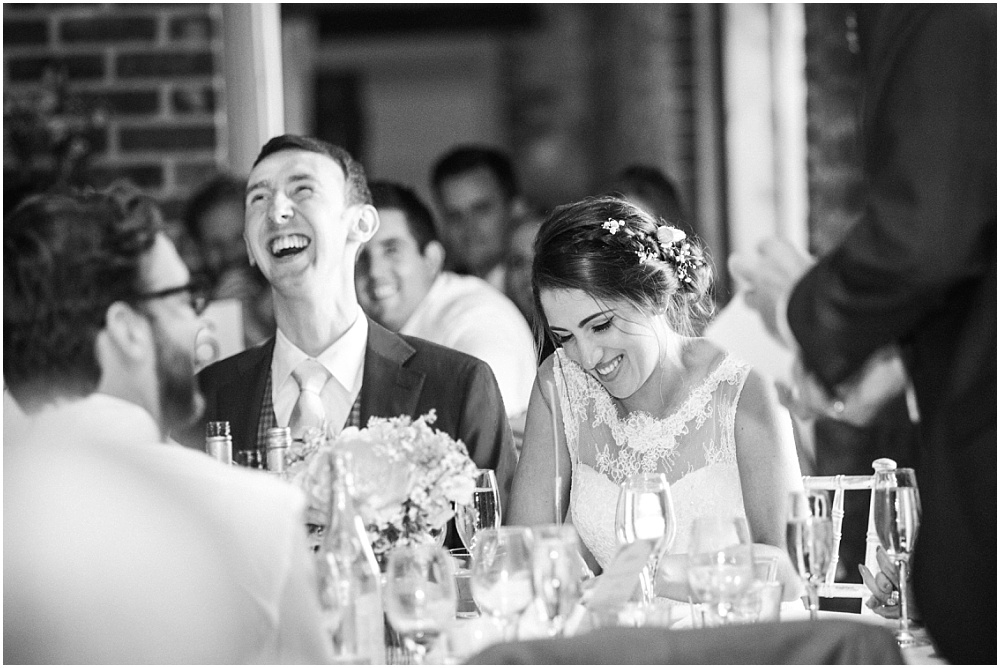 Bride and groom laugh during wedding speeches