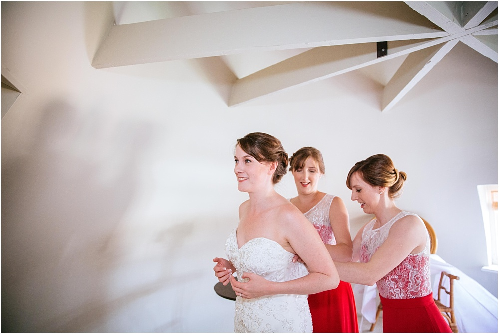 Bridesmaids help bride with wedding dress