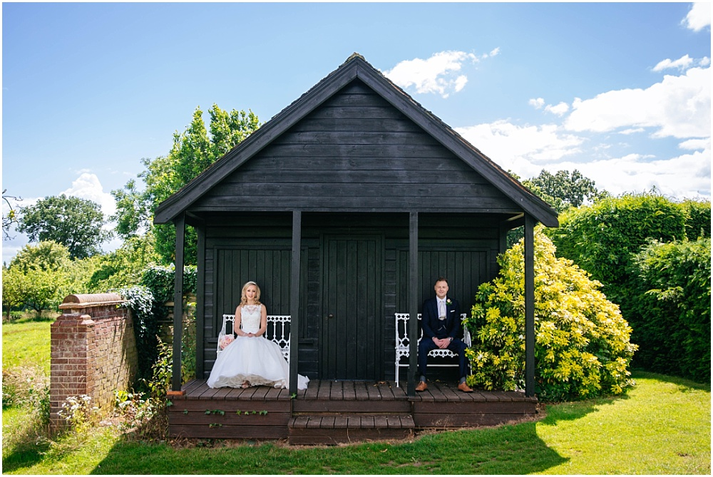 Bride and groom in front of black shed