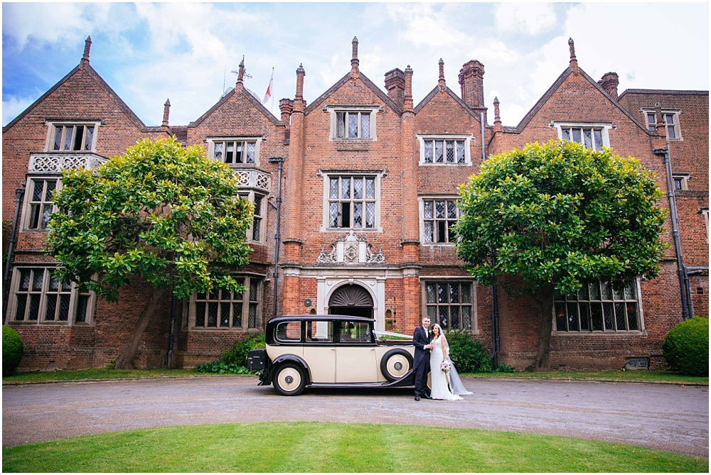Bride and groom and vintage car in front of great fosters