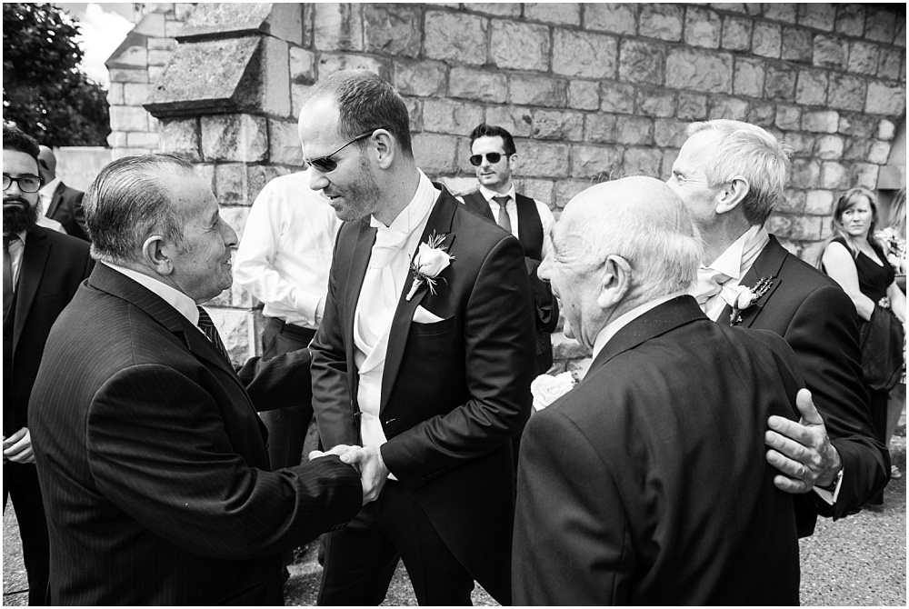 Groom greeting guests outside church