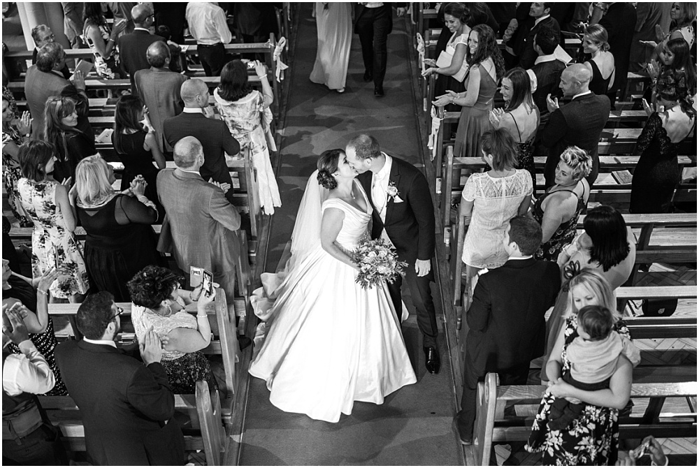Bride and groom kissing as back back down aisle