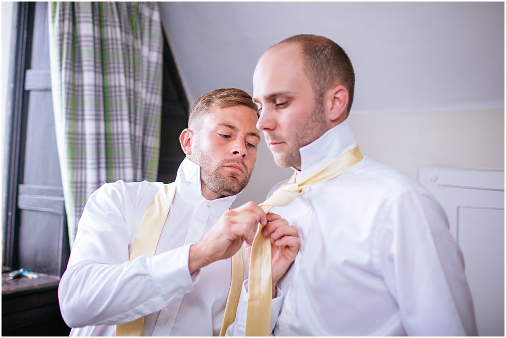 Groomsman concentrating on doing up tie