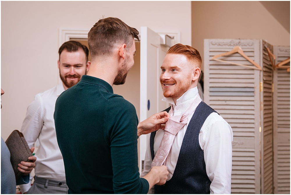 Groom putting his grooms tie on