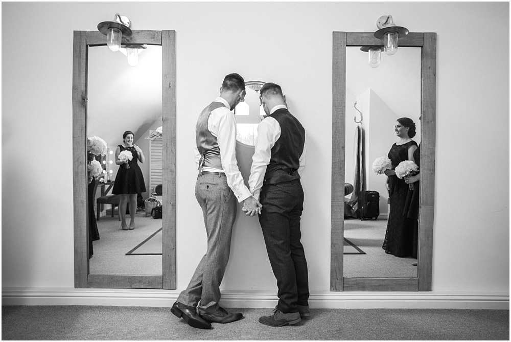 Two grooms hold hand before gay wedding