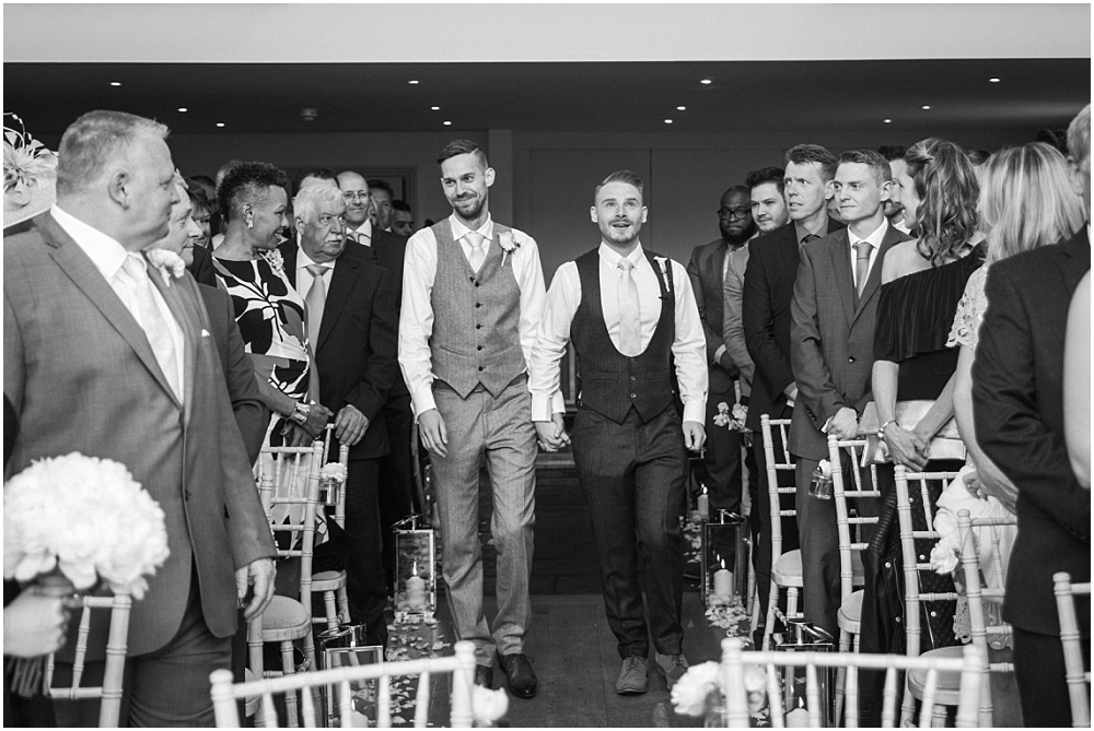 Two grooms walk down aisle together millbridge court