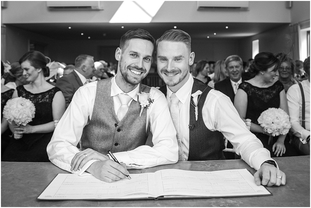 Handsome grooms signing the register