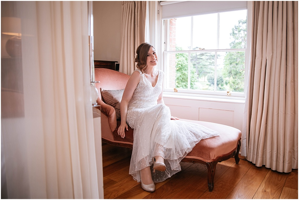 Bride on chaise long in bridal suite in the grove