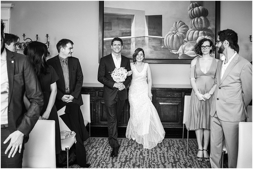 Bride and groom walk down aisle together with groom holding paper bouquet