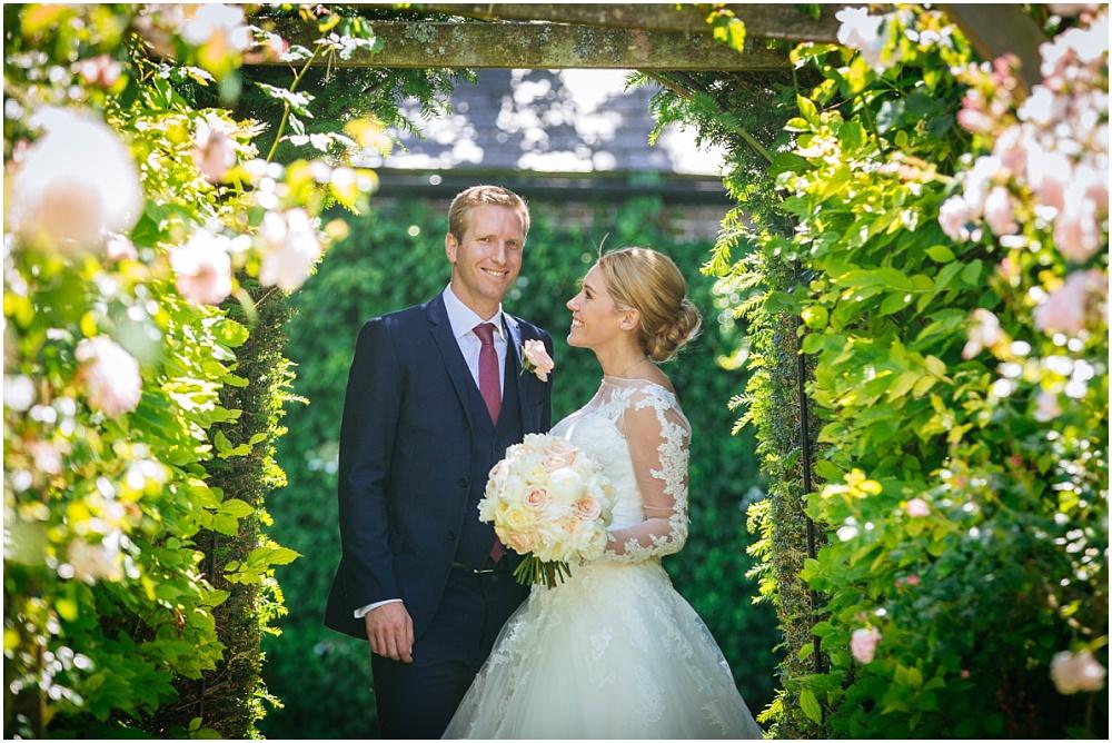 Bride looking at groom in rose garden