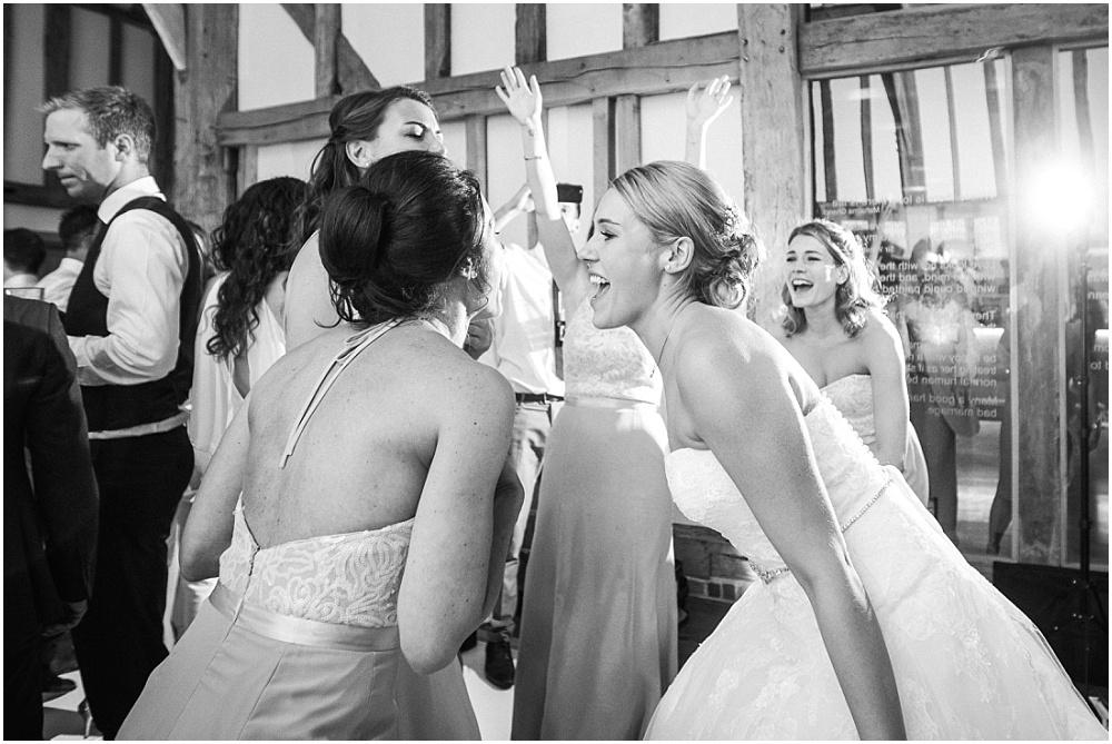 Bridesmaid and bride dancing