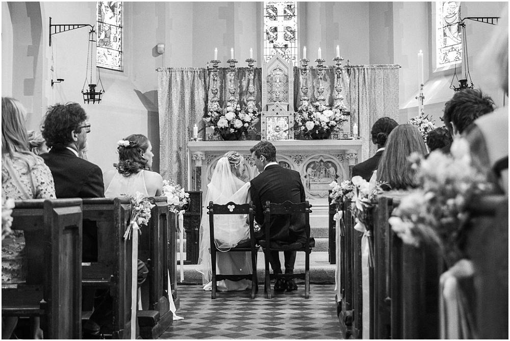 Groom whispering to bride in church wedding
