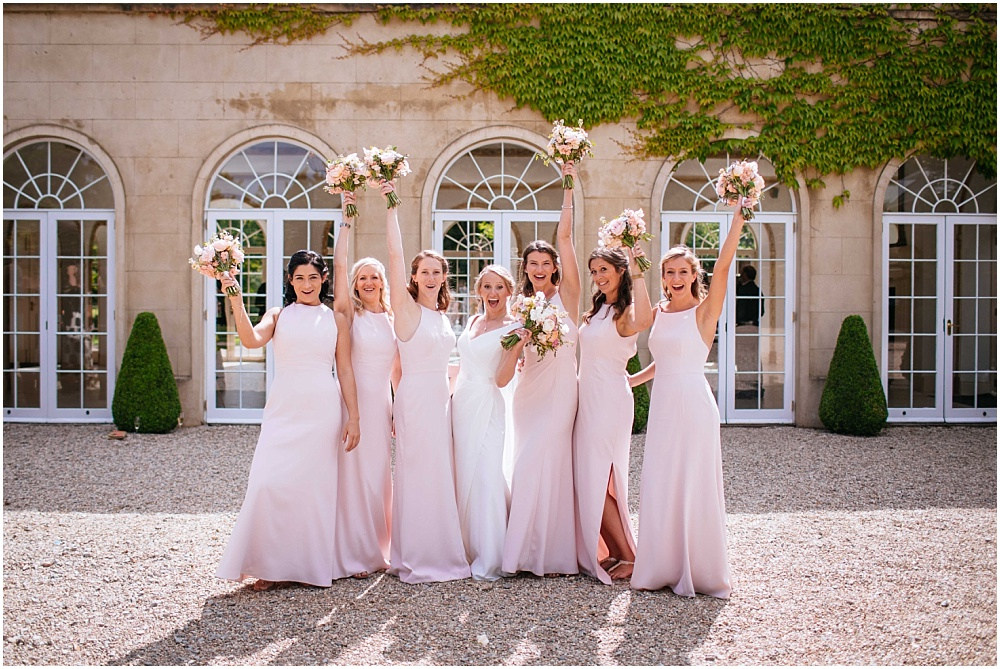 Bridesmaids in pink waving bouquets