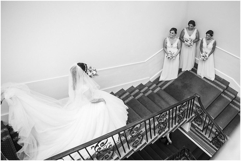 bridesmaids seeing bride on stairs