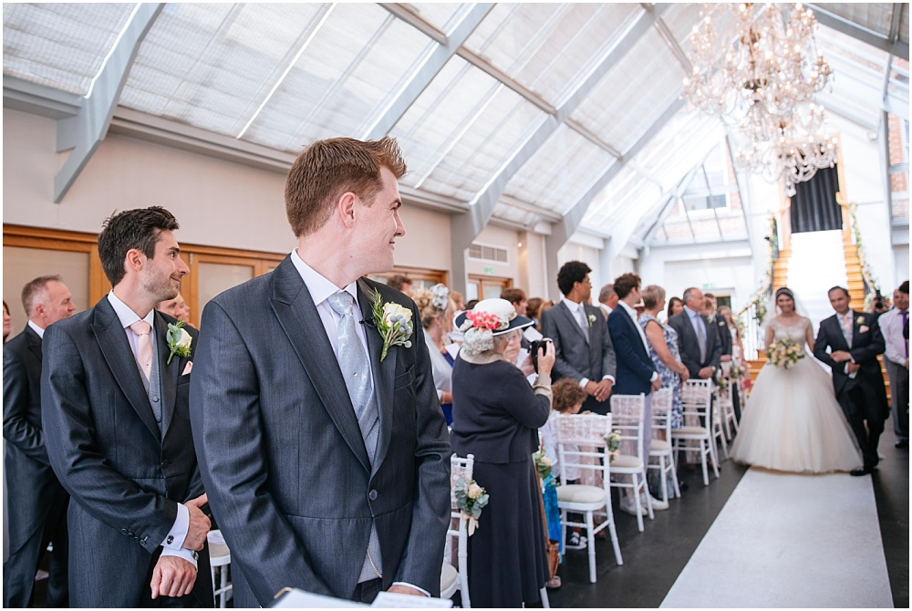 groom delighted face as sees beautiful bride walk down the aisle