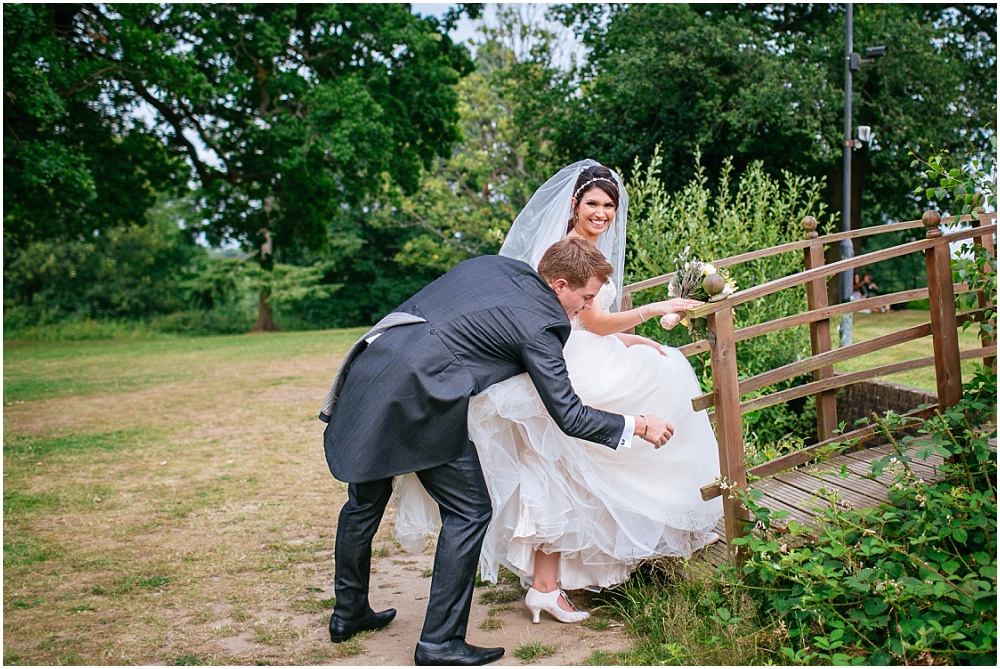 Groom helping bride with dress