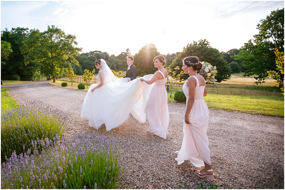 Bridesmaids helping with dress in golden hour