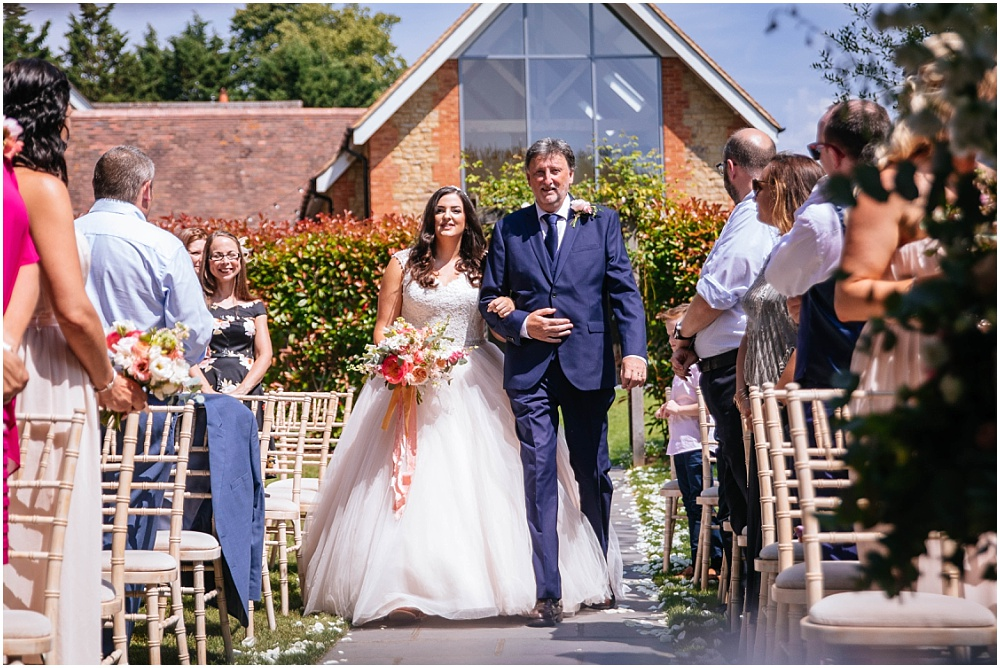 Bride and dad walk down outdoor aisle