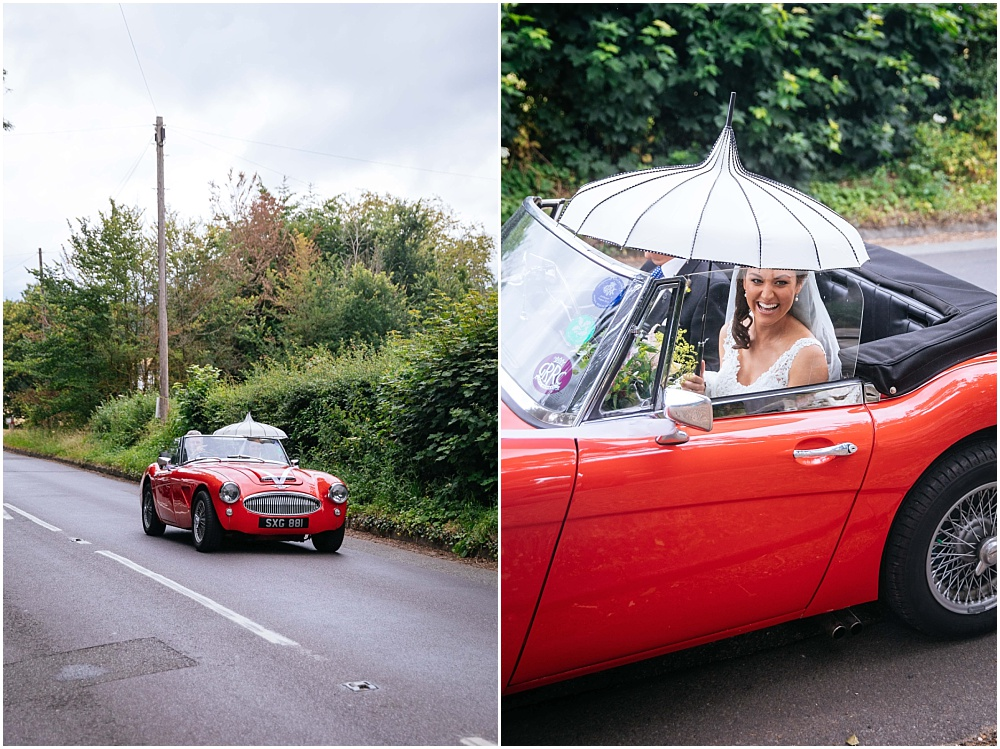Bride arrives in red sports car with umbrella