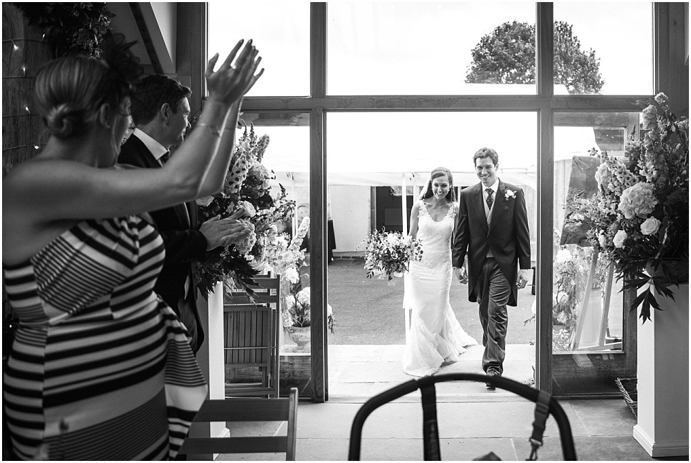 Bride and groom entering barn for wedding breakfast