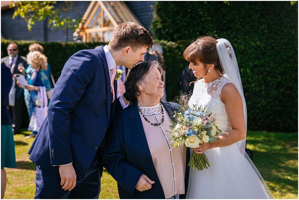 Bride and groom greeting grandma