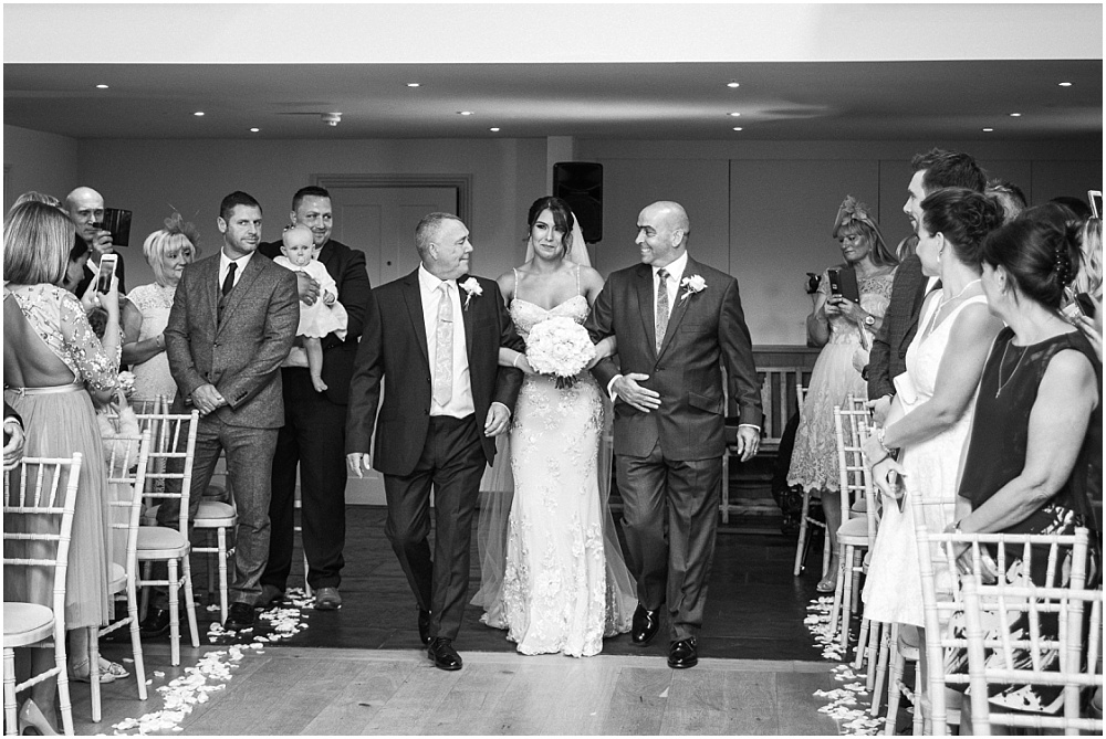 Bride walking down the aisle with bride and stepdad