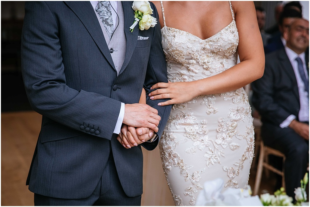 Bride and groom clasping hands during ceremony